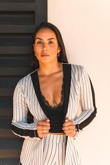 Steilharige brunette vrouw in een wit pak en zwarte strepen