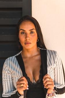 Steilharige brunette vrouw in een wit pak met zwarte strepen