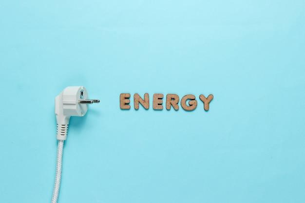 Stekker met het woord energie op blauw oppervlak.