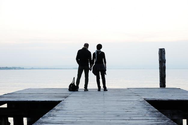 Stel bij het houten dok op een prachtig meer