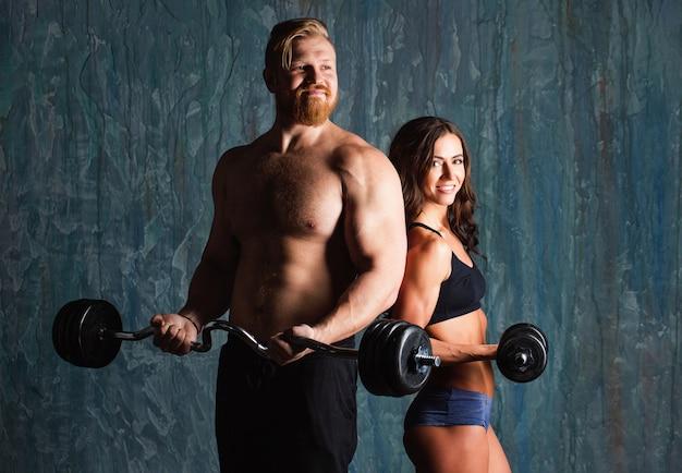 Stel bodybuilders. mannelijke en vrouwelijke bodybuilders met halters en halters.