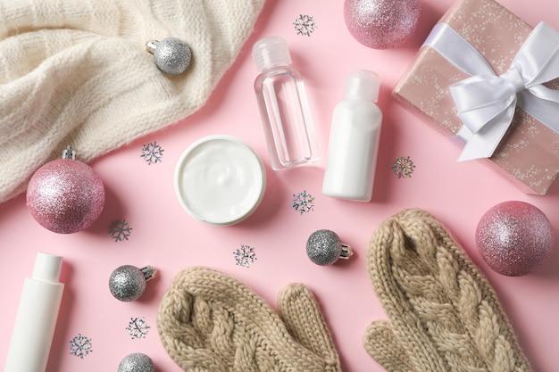 Stel cosmetica, wintercrème voor de huid, warme trui en handschoenen op roze, ruimte voor tekst. bovenaanzicht