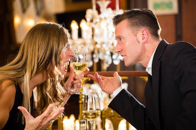 Stel heeft ruzie over een romantisch date fine dining restaurant, ze zijn boos en schreeuwen, een grote kroonluchter