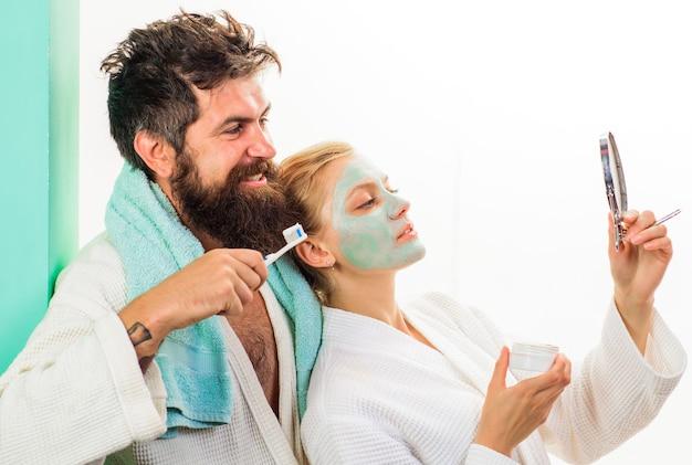 Stel in de badkamer. ochtendfamilie. vrouw met cosmetisch gezichtsmasker, echtgenoot met tandenborstel.