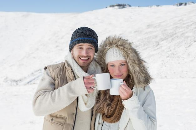 Stel in warme kleding met koffiekoppen op gesneeuwd landschap