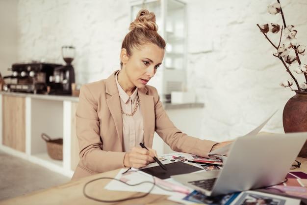 Stel je eens voor. gerichte modeontwerper die een vel papier en een stylus vasthoudt en naar haar laptop kijkt en nieuwe schetsen maakt.