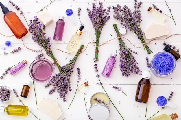 Stel lavendel cosmetische schoonheid apotheek medicijnen badproducten en lavendel bloemen. serumzeep zeezout etherische olie, body butter, massageolie, vloeistof. plat lag witte houten achtergrond. huidverzorging spa.