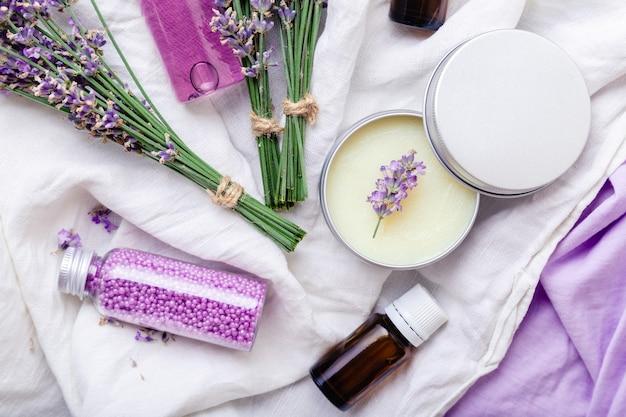 Stel lavendel huidverzorging cosmetica producten. natuurlijke spa schoonheidsproducten verse lavendel bloemen op stof. lavendel etherische olie fles body butter massage olie crème zeep bad kralen gel vloeistof. plat leggen