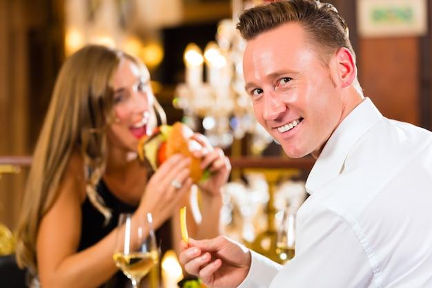 Stel, man en vrouw een fine dining restaurant ze eten fastfood, hamburger en friet