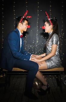 Stel met hertengeweien hoofdbanden en grappige neuzen tussen tossende confetti