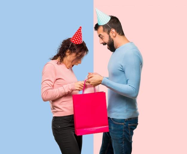 Stel met verjaardagshoeden en met boodschappentassen op roze en blauwe achtergrond