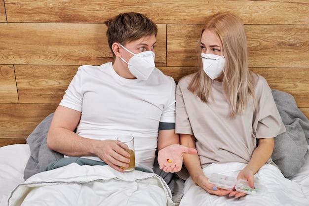 Stel thuis met covid-19-ziekte op bed die medicijnen nemen, elkaar steunen en helpen, thuis zitten bespreken. coronavirus, covid-19, ziekteconcept
