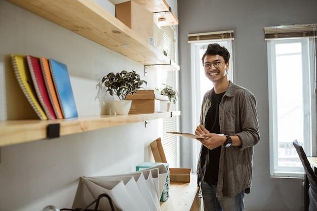 Stel van glimlachende jonge aziatische ondernemer wanneer houd een klembord