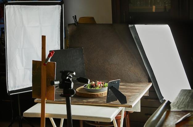 Stel voedselfotograafapparatuur in voor het fotograferen van recepten, softboxen en statieven, reflectoren en achtergronden.