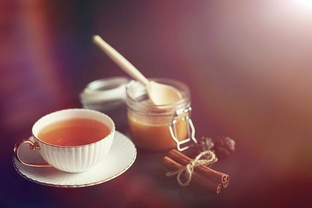 Stel voor het ontbijt. snoep en gebak met noten voor thee op zwarte achtergrond. een kopje koffie en pasteitjes.