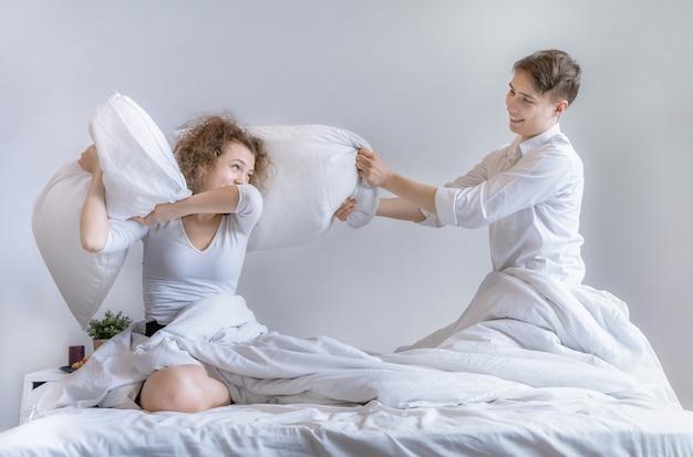 Stellen gebruiken een kussen om elkaar op het bed te plagen.