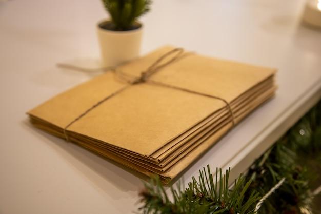 Stelletje brieven aan de kerstman gemaakt van ambachtelijk papier vastgebonden met een touw liggen naast kerstmis