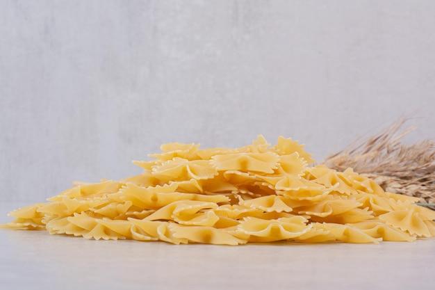 Stelletje farfalle pasta op witte tafel met tarwe.