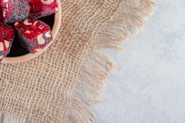 Stelletje gedroogde rode fruitpulp met noten in keramische kom.