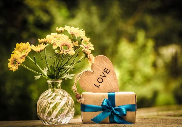 Stelletje gele bloemen, cadeau en houten hart