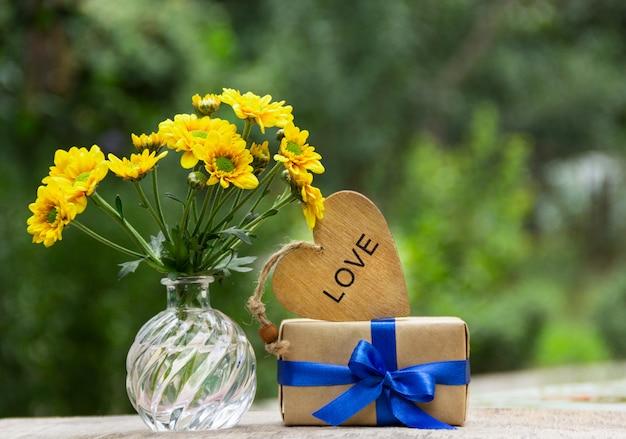 Stelletje gele bloemen, cadeau en houten hart.