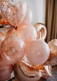 Stelletje glimmende roze ballonnen met helium in huis