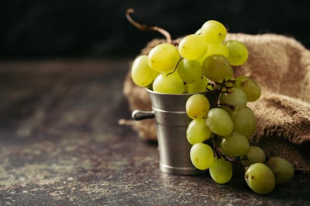 Stelletje groene druiven op een donkere achtergrond.