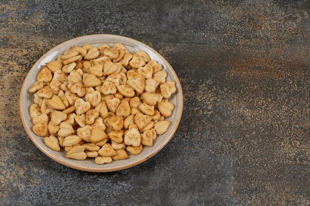 Stelletje hartvormige crackers op keramische plaat.