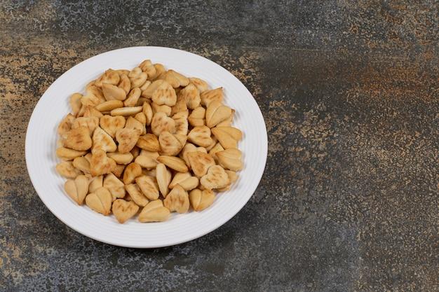 Stelletje hartvormige crackers op witte plaat.