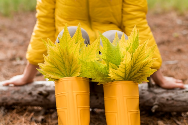 Stelletje herfstbladeren in gele regenlaarzen