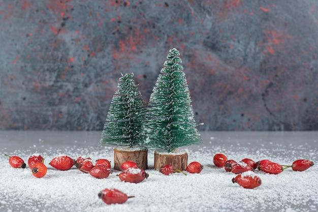 Stelletje heupen, kokospoeder en kerstboombeeldjes op marmeren tafel.