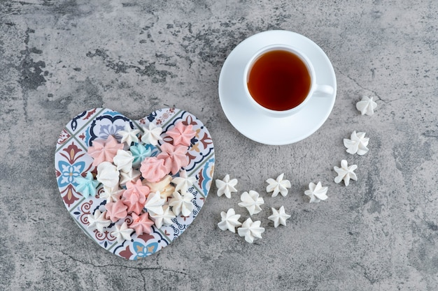 Stelletje kleurrijke meringue snoepjes op hartvormige onderzetter en kopje thee.