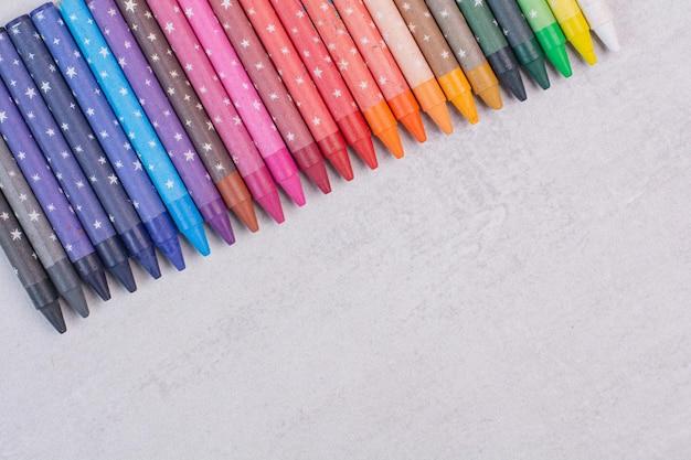 Stelletje kleurrijke potloden op witte ondergrond.