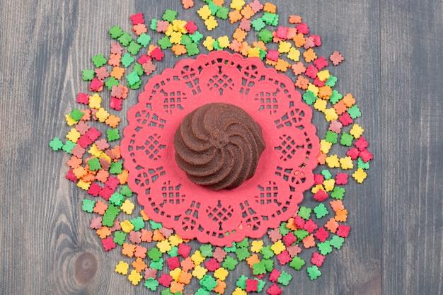 Stelletje kleurrijke snoepjes rond chocoladekoekje