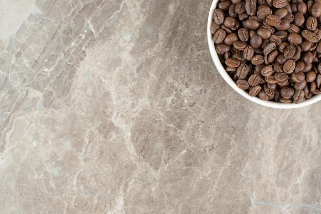 Stelletje koffiebonen in witte kom