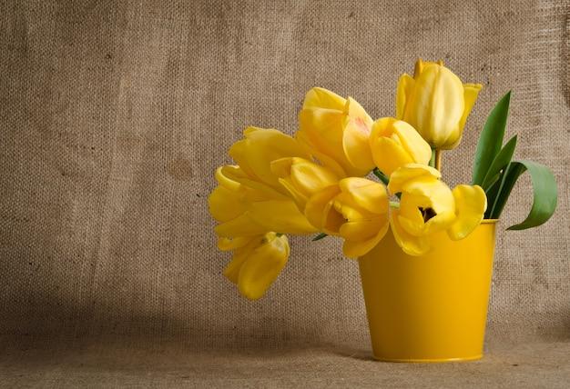 Stelletje mooie felgele tulpen in een pot op jute achtergrond