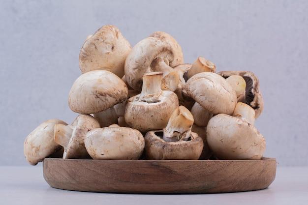Stelletje rauwe champignons op houten plaat.