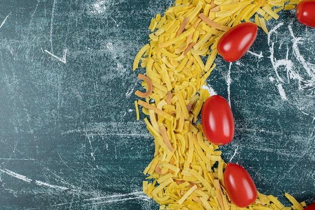 Stelletje rauwe pasta op blauwe ruimte met tomaten.
