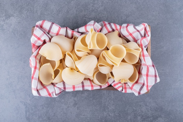 Stelletje rauwe shell pasta in houten kist.