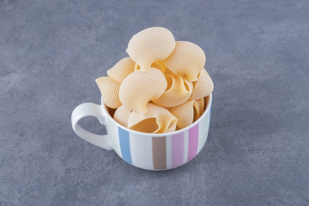 Stelletje rauwe shell pasta in mok.