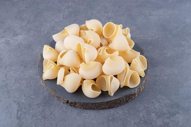 Stelletje rauwe shell pasta op stuk hout.