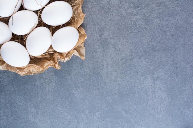 Stelletje rauwe witte eieren op stenen tafel.