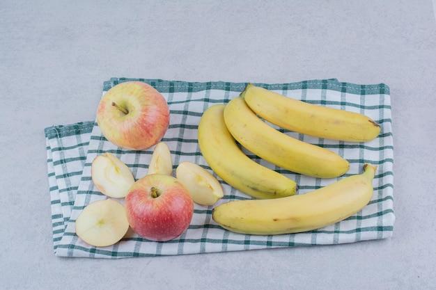 Stelletje rijpe fruitbananen met gesneden appel op tafellaken. hoge kwaliteit foto