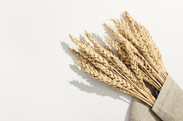 Stelletje rijpe tarwe oren close-up op wit en zak. creatieve herfstoogst van graangewassen.