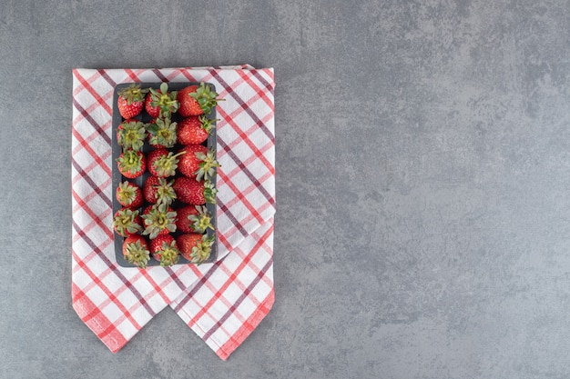 Stelletje rode aardbeien op zwarte plaat. hoge kwaliteit foto