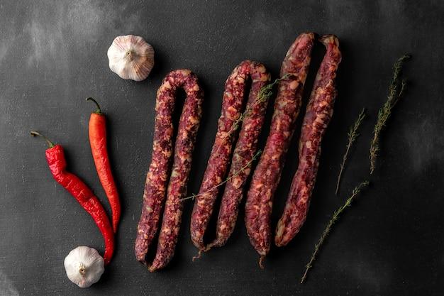 Stelletje rode droge zelfgemaakte worstjes en knoflook op een donkere achtergrond, bovenaanzicht