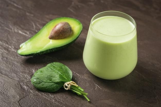 Stelletje spinaziebladeren, avocado en smoothies op een stenen ondergrond. fitnessproduct. dieet sportvoeding.