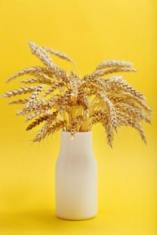 Stelletje tarweoren in witte vaas close-up op geel papier herfstoogst van graangewassen