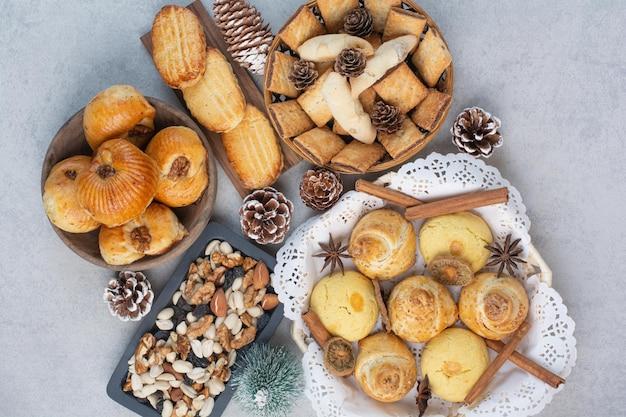Stelletje verschillende koekjes, noten en dennenappels in kommen. hoge kwaliteit foto