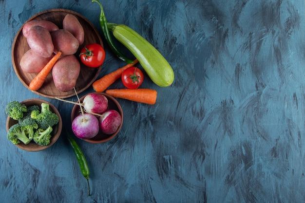 Stelletje verschillende verse groenten op blauwe achtergrond.